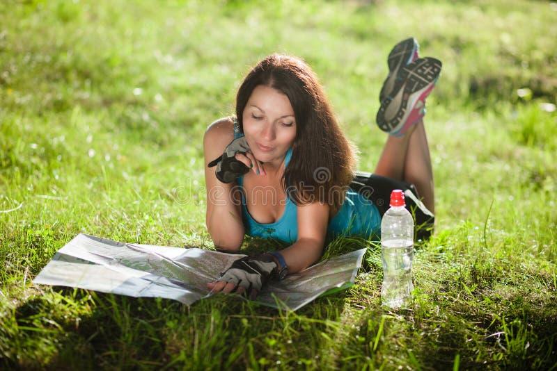 Το κορίτσι αθλητικού ταξιδιού βάζει σε μια χλόη και διάβασε έναν χάρτη στοκ εικόνες με δικαίωμα ελεύθερης χρήσης