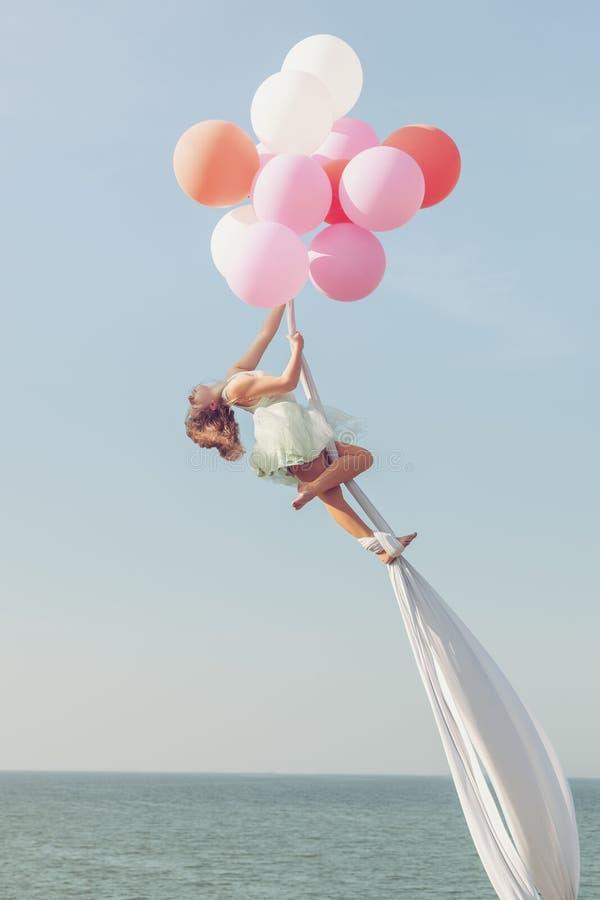 Το κορίτσι αιωρείται στον αέρα από τα μπαλόνια στοκ φωτογραφία