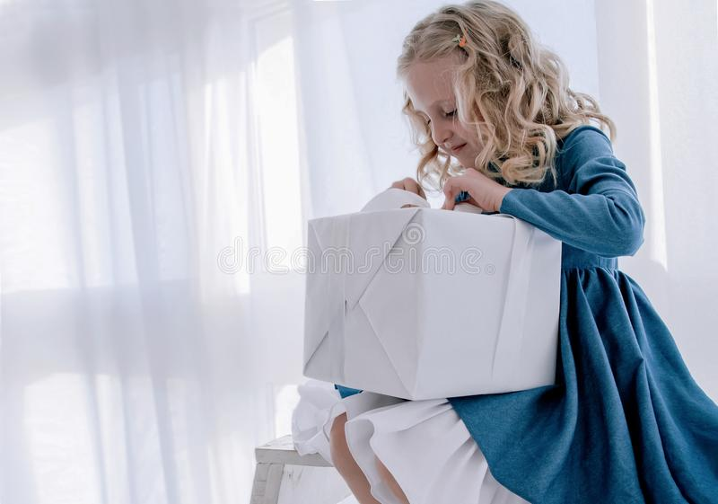 Το κορίτσι ανοίγει το κιβώτιο δώρων στοκ εικόνες