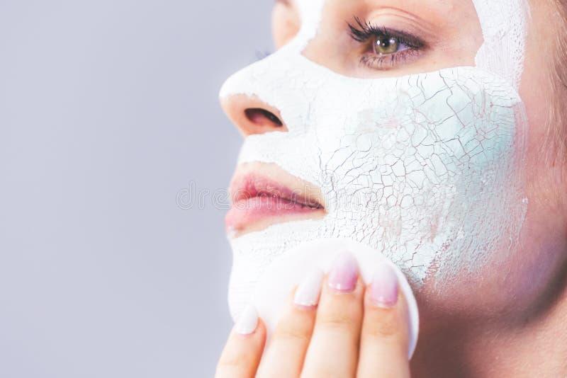 Το κορίτσι αφαιρεί την ξηρά άσπρη μάσκα λάσπης στοκ εικόνα με δικαίωμα ελεύθερης χρήσης