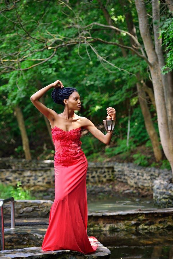 Το κορίτσι αφροαμερικάνων σε ένα κόκκινο φόρεμα, με έναν λαμπτήρα και ένα κερί στο χέρι του στέκεται στο πάρκο κοντά στο νερό στοκ εικόνες