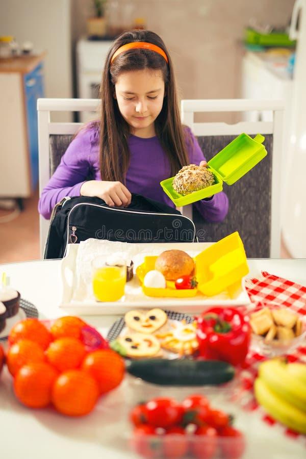 Το κορίτσι βάζει ένα πρόχειρο φαγητό σε μια τσάντα για το σχολείο στοκ φωτογραφία με δικαίωμα ελεύθερης χρήσης