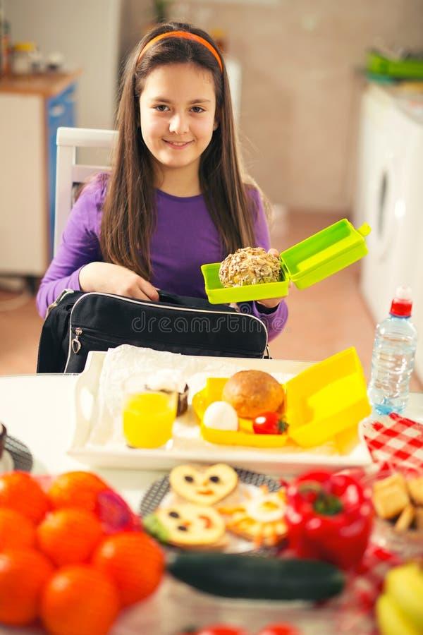 Το κορίτσι βάζει ένα πρόχειρο φαγητό σε μια τσάντα για το σχολείο στοκ εικόνες