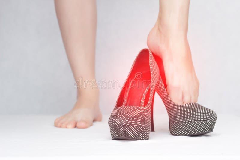 Το κορίτσι βάζει στα μολυσματικά παπούτσια με μια μυκητιακή μόλυνση και mycosis, κινηματογράφηση σε πρώτο πλάνο, άσπρο υπόβαθρο,  στοκ φωτογραφία με δικαίωμα ελεύθερης χρήσης