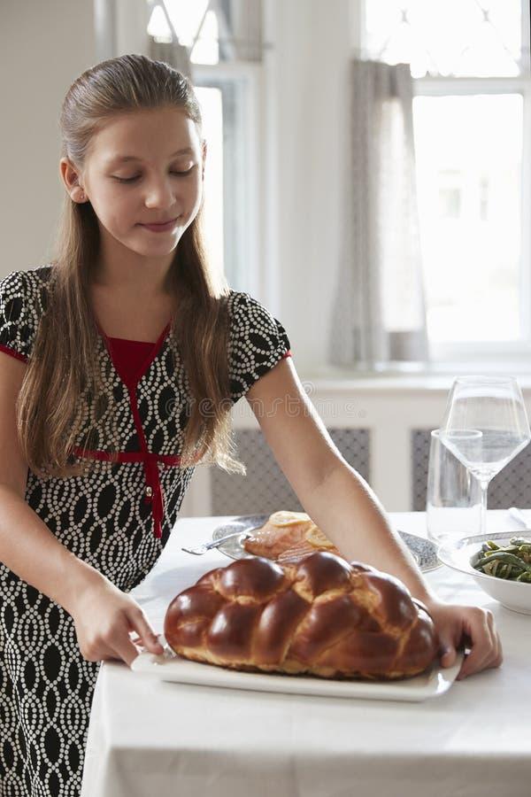 Το κορίτσι βάζει challah το ψωμί στον πίνακα για το γεύμα Shabbat, κάθετο στοκ εικόνα