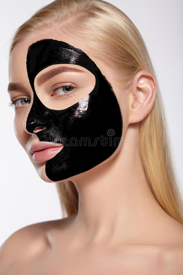 Το κορίτσι βγάζει τη μαύρη καλλυντική μάσκα από το πρόσωπό της στοκ εικόνες