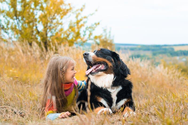το κορίτσι βρίσκεται δίπλα στο μεγάλο σκυλί στον περίπατο φθινοπώρου στοκ εικόνα