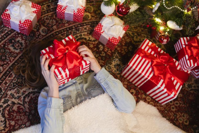 Το κορίτσι βρίσκεται στα δώρα κάτω από το χριστουγεννιάτικο δέντρο στοκ εικόνες