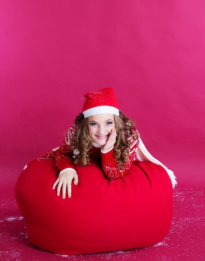 Το κορίτσι βρίσκεται στη μεγάλη κόκκινη τσάντα Χριστουγέννων στοκ φωτογραφία με δικαίωμα ελεύθερης χρήσης