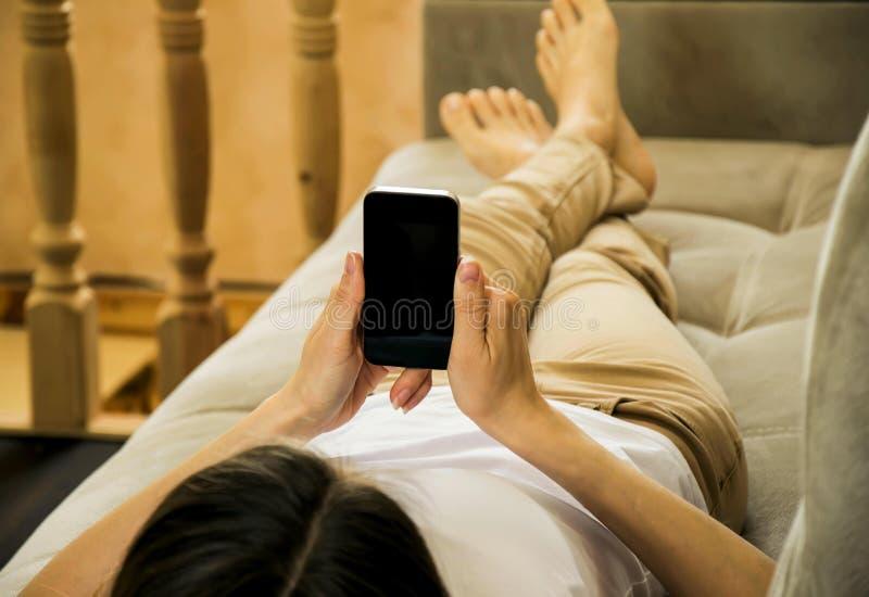 Το κορίτσι βρίσκεται στον καναπέ και διαβάζει τις ειδήσεις και τα μηνύματα στο τηλέφωνο στοκ φωτογραφία με δικαίωμα ελεύθερης χρήσης