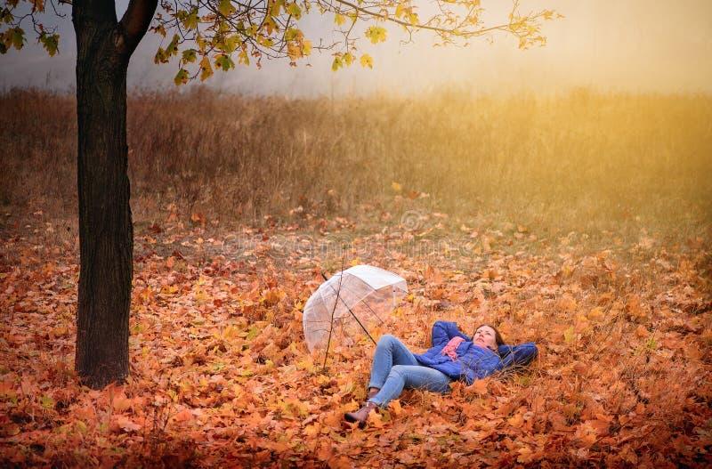 Το κορίτσι βρίσκεται στο φύλλωμα φθινοπώρου στοκ εικόνες με δικαίωμα ελεύθερης χρήσης