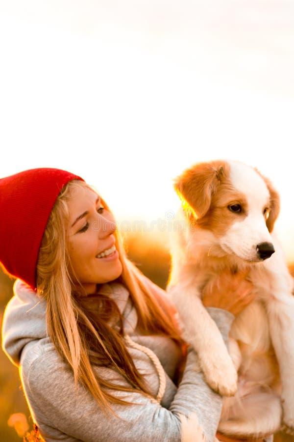 Το κορίτσι γέλιου με το δροσερό κουτάβι σκυλιών κόλλεϊ συνόρων παραδίδει επάνω τον πράσινο τομέα ηλιοβασίλεμα ουρανού στο υπόβαθρ στοκ εικόνες