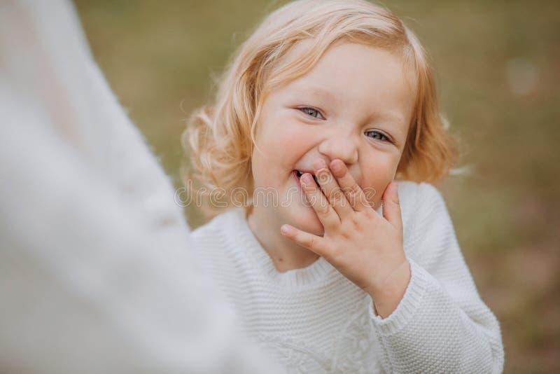 το κορίτσι γελά πάρκο περιπάτων χεριών προσώπου καλύψεων mom στοκ φωτογραφία