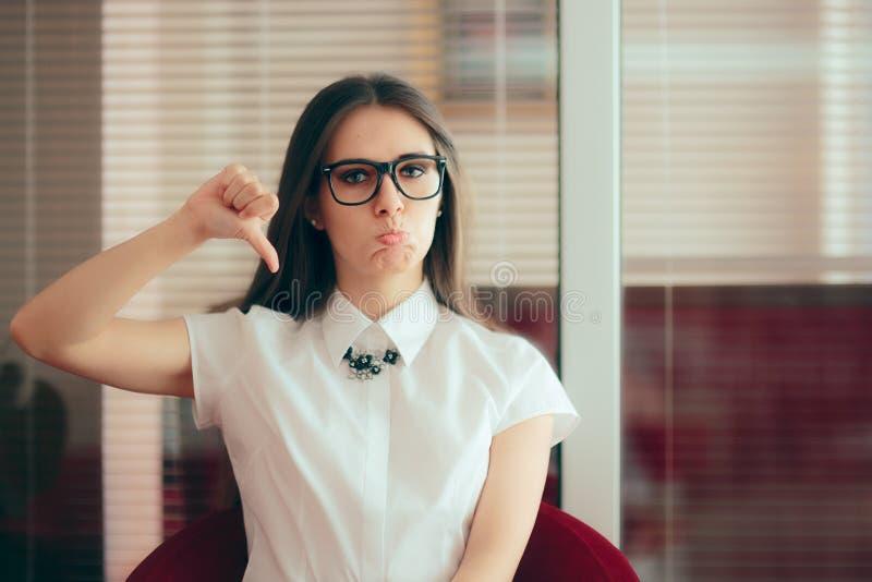 Το κορίτσι γραφείων με τους αντίχειρες αντιπαθεί κάτω τη χειρονομία της αποδοκιμασίας στοκ εικόνα με δικαίωμα ελεύθερης χρήσης