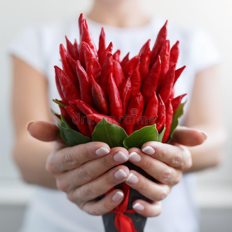 Το κορίτσι δίνει μια μικρή ανθοδέσμη φιαγμένη από κόκκινο - καυτά πιπέρια υπό μορφή καρδιάς στοκ εικόνες με δικαίωμα ελεύθερης χρήσης