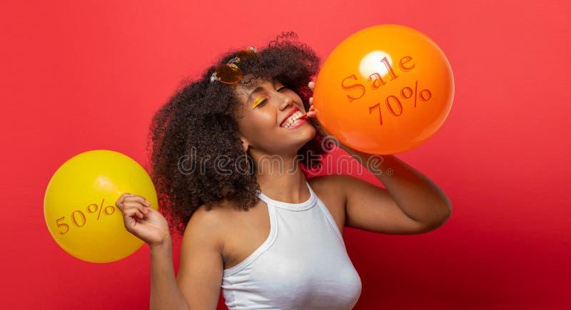 Το κορίτσι διογκώνει τα μπαλόνια με τις εκπτώσεις στοκ φωτογραφίες