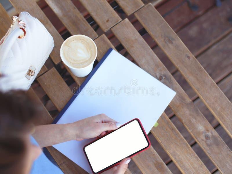 Το κορίτσι δουλεύει για ένα φλιτζάνι καφέ Κενό για σχεδιαστές με τηλέφωνο στοκ εικόνες