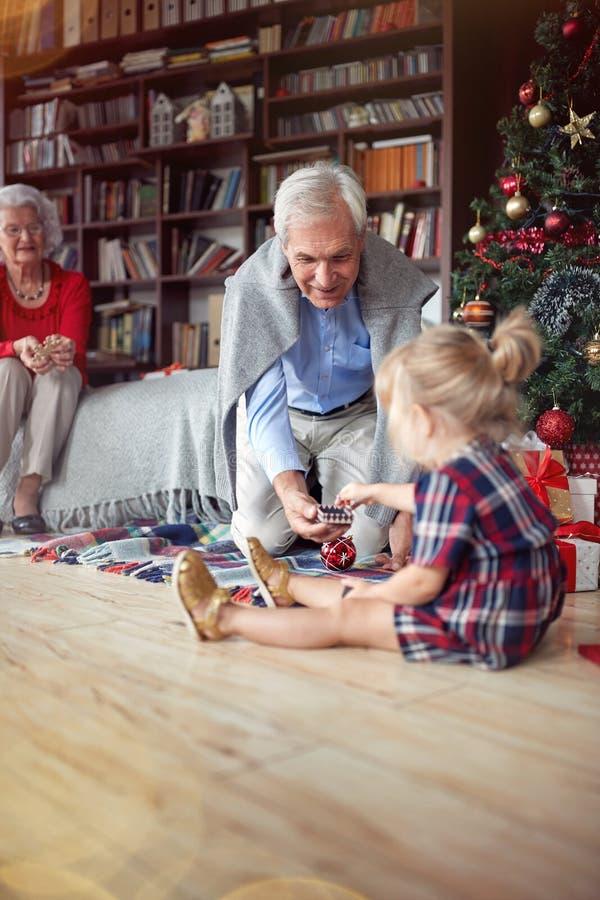 Το κορίτσι είναι ανοικτό χριστουγεννιάτικο δώρο μπροστά από ένα διακοσμημένο χριστουγεννιάτικο δέντρο με το grandpa στοκ εικόνες