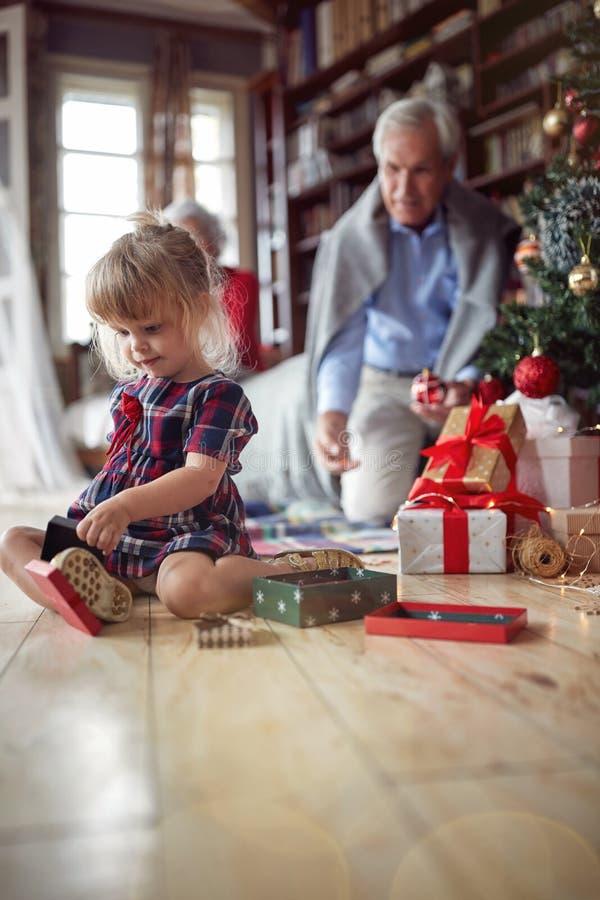 Το κορίτσι είναι ανοικτό χριστουγεννιάτικο δώρο μπροστά από ένα διακοσμημένο χριστουγεννιάτικο δέντρο στοκ φωτογραφίες με δικαίωμα ελεύθερης χρήσης