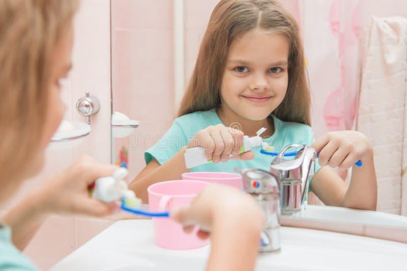 Το κορίτσι εξάχρονων παιδιών συμπιέζει την οδοντόπαστα από έναν σωλήνα στην οδοντόβουρτσα στοκ φωτογραφία με δικαίωμα ελεύθερης χρήσης