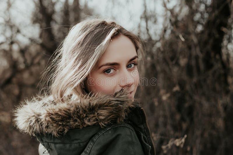 Το κορίτσι εξετάζει πέρα από τον ώμο της τη κάμερα στο θερμό σακάκι στοκ φωτογραφία με δικαίωμα ελεύθερης χρήσης