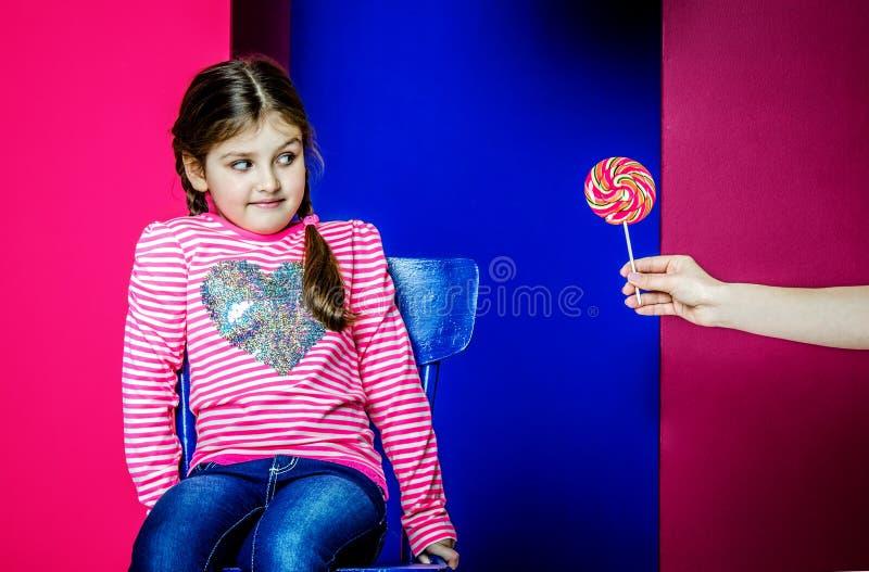Το κορίτσι εξετάζει την καραμέλα που προσφέρεται σε της στοκ φωτογραφία με δικαίωμα ελεύθερης χρήσης