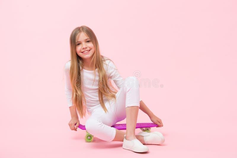 Το κορίτσι επιθυμεί να οδηγήσει skateboard Ενεργός τρόπος ζωής Κορίτσι που έχει τη διασκέδαση με το ρόδινο υπόβαθρο πινάκων πενών στοκ φωτογραφία