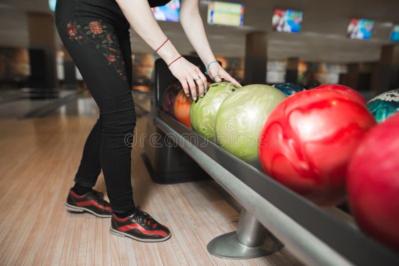 Το κορίτσι επιλέγει ένα χρωματισμένο κύπελλο για να παίξει το μπόουλινγκ πρίν ρίχνει πλησιάζοντας καρφίτσες παιχνιδιών μπόουλινγκ στοκ εικόνες