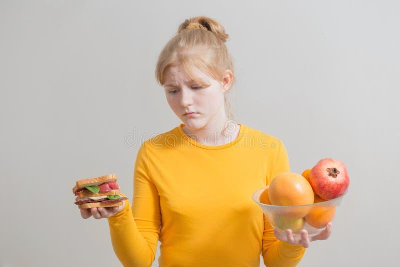 Το κορίτσι επιλέγει μεταξύ των υγιών και ανθυγειινών τροφίμων στοκ εικόνα με δικαίωμα ελεύθερης χρήσης