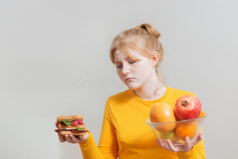 Το κορίτσι επιλέγει μεταξύ των υγιών και ανθυγειινών τροφίμων στοκ φωτογραφίες