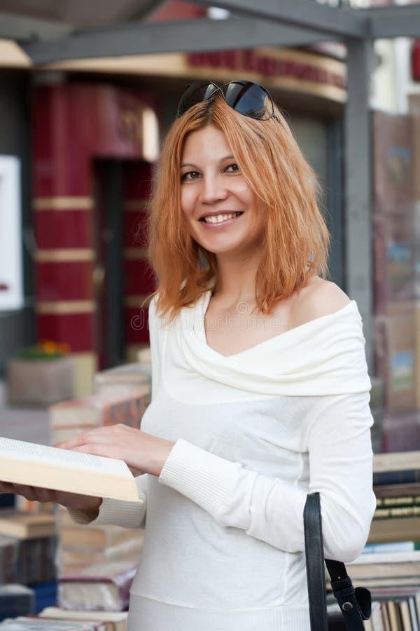 Το κορίτσι επιλέγει το βιβλίο στοκ εικόνα