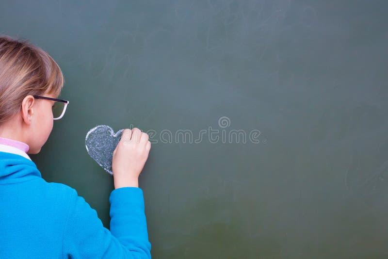 Το κορίτσι επισύρει την προσοχή την καρδιά μια κιμωλία σε έναν πίνακα Ελεύθερου χώρου για το κείμενο insertion_ στοκ εικόνα