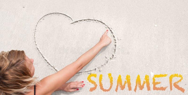 Το κορίτσι επισύρει την προσοχή την καρδιά στην άμμο στοκ εικόνα με δικαίωμα ελεύθερης χρήσης