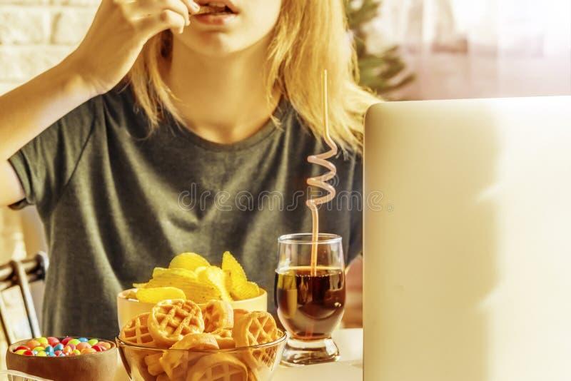 Το κορίτσι εργάζεται σε έναν υπολογιστή και τρώει το γρήγορο φαγητό στοκ φωτογραφίες με δικαίωμα ελεύθερης χρήσης