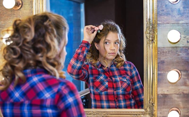 Το κορίτσι εφήβων είναι μπροστά από τον καθρέφτη που προσπαθεί στο λουλούδι στοκ εικόνες