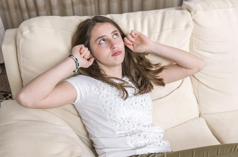 Το κορίτσι εφήβων καλύπτει τη συνεδρίαση χειρονομίας αυτιών της στον καναπέ στο σπίτι στοκ φωτογραφία