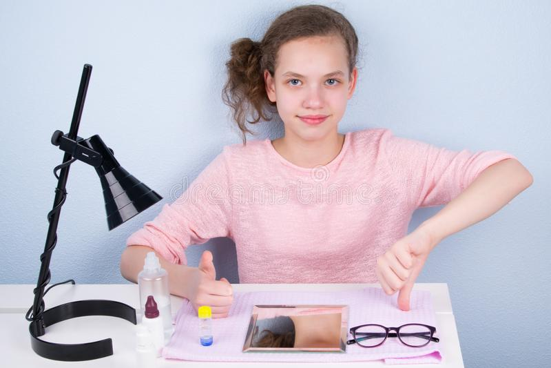 Το κορίτσι εφήβων παρουσιάζει χέρια της καλά και κακός, στον πίνακα γυαλιά και φακοί για να βελτιώσετε το όραμα στοκ φωτογραφία με δικαίωμα ελεύθερης χρήσης
