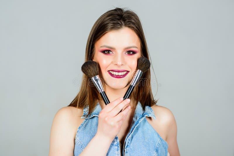 Το κορίτσι εφαρμόζει τις σκιές ματιών Γυναίκα που εφαρμόζει makeup τη βούρτσα Υπογραμμίστε τη θηλυκότητα Διαφορετικές βούρτσες Επ στοκ φωτογραφία με δικαίωμα ελεύθερης χρήσης
