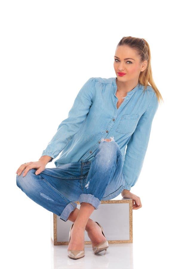 Το κορίτσι θέτει καθισμένος στο υπόβαθρο στούντιο με το χέρι στην κλίση γονάτων στοκ φωτογραφίες με δικαίωμα ελεύθερης χρήσης
