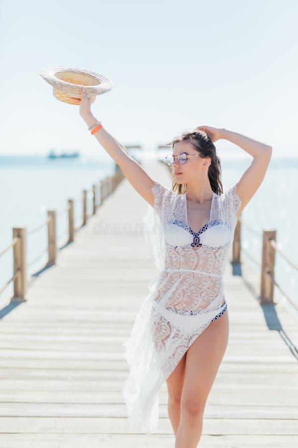 Το κορίτσι θέτει την εν πλω αποβάθρα στο καπέλο αχύρου και τα γυαλιά ηλίου Γυναίκα στο προκλητικό μαγιό στην τροπική παραλία στον στοκ φωτογραφίες