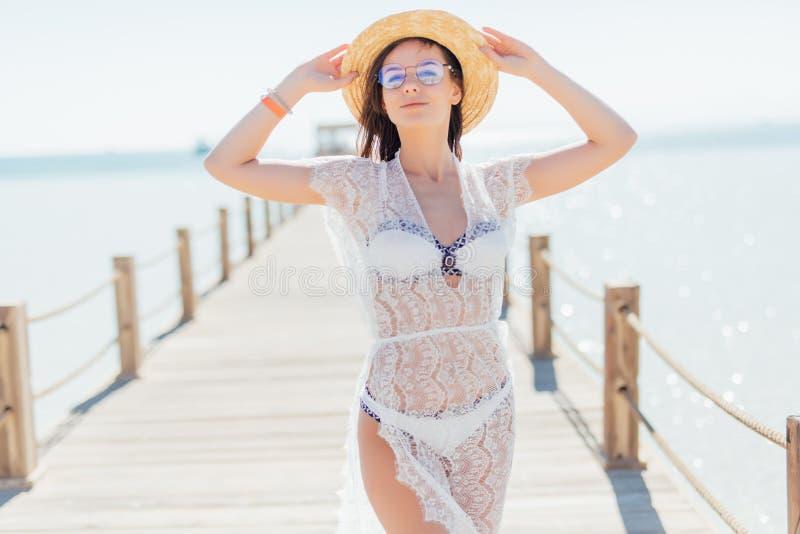 Το κορίτσι θέτει την εν πλω αποβάθρα στο καπέλο αχύρου και τα γυαλιά ηλίου Γυναίκα στο προκλητικό μαγιό στην τροπική παραλία στον στοκ εικόνες με δικαίωμα ελεύθερης χρήσης