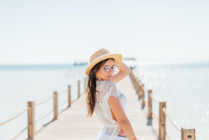 Το κορίτσι θέτει την εν πλω αποβάθρα στο καπέλο αχύρου και τα γυαλιά ηλίου Γυναίκα στο προκλητικό μαγιό στην τροπική παραλία στον στοκ εικόνες