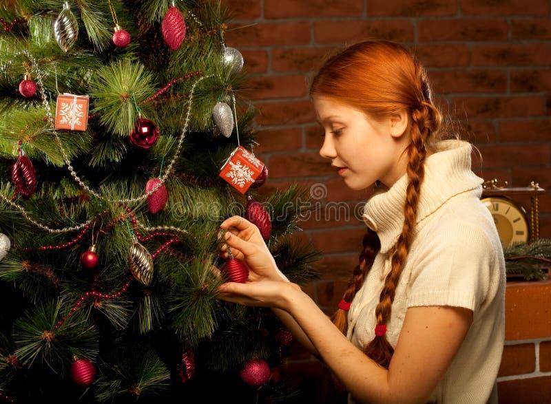 Το κορίτσι διακοσμεί το χριστουγεννιάτικο δέντρο στοκ εικόνες