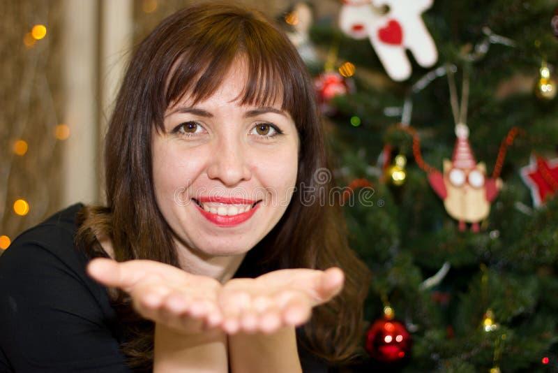 Το κορίτσι κάθεται κοντά σε ένα χριστουγεννιάτικο δέντρο στοκ εικόνα