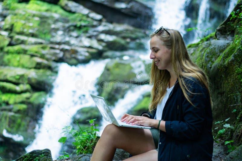 Το κορίτσι κάθεται με ένα lap-top και εργάζεται ενάντια στο σκηνικό ενός καταρράκτη στοκ φωτογραφίες