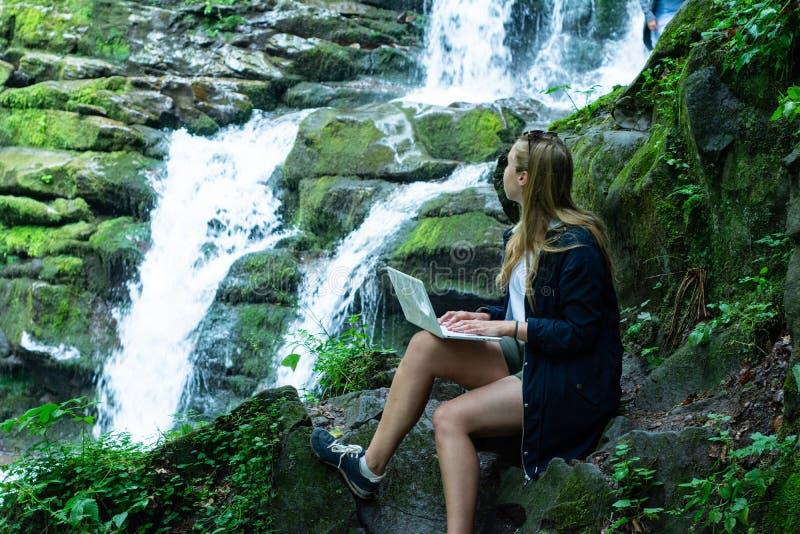 Το κορίτσι κάθεται με ένα lap-top και εργάζεται ενάντια στο σκηνικό ενός καταρράκτη στοκ εικόνες