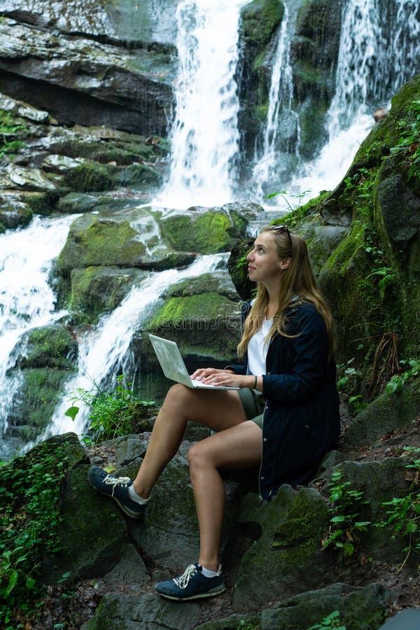Το κορίτσι κάθεται με ένα lap-top και εργάζεται ενάντια στο σκηνικό ενός καταρράκτη στοκ φωτογραφία με δικαίωμα ελεύθερης χρήσης