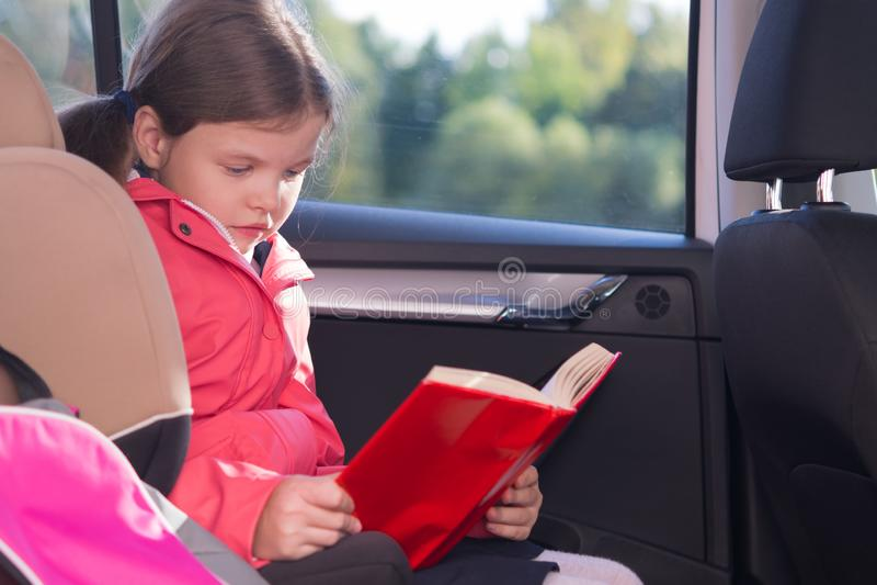 το κορίτσι κάθεται σε ένα κάθισμα αυτοκινήτων που κρατά έναν γύρο διαβάζοντας ένα κόκκινο βιβλίο κάλυψης στοκ εικόνες με δικαίωμα ελεύθερης χρήσης