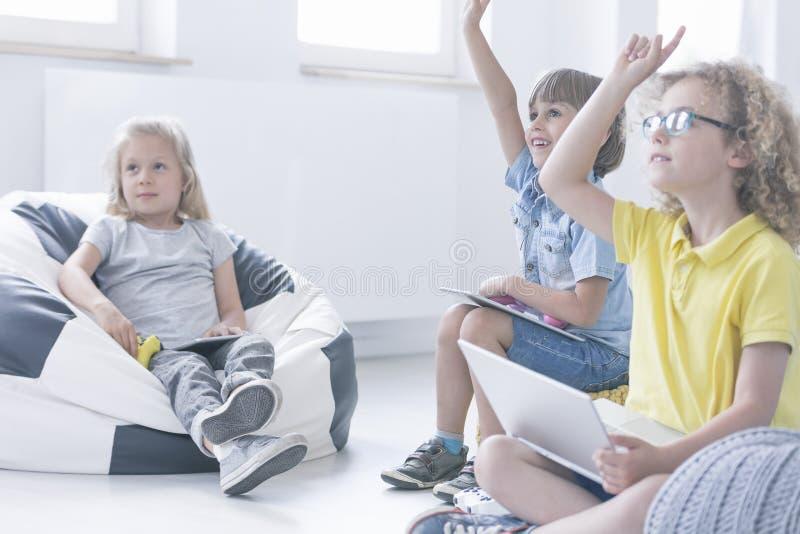 Το κορίτσι κάθεται σε ένα μαξιλάρι πουφ στοκ εικόνες