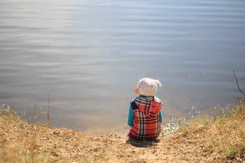 Το κορίτσι κάθεται στην ακτή και τα όνειρα στοκ φωτογραφία με δικαίωμα ελεύθερης χρήσης